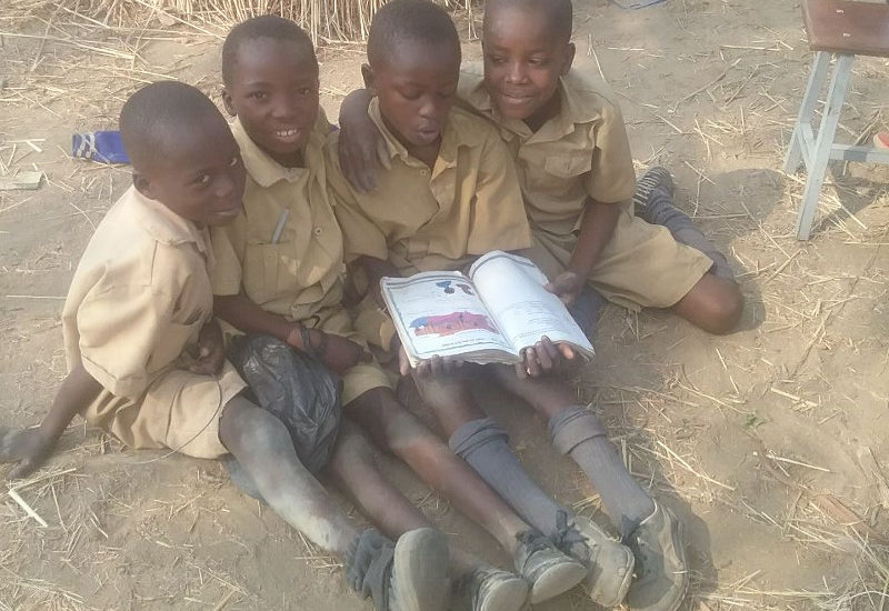 Picture of four boys sharin one book